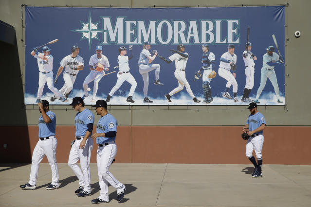 Seattle Mariners players walk to a practice field during spring training baseball practice Tuesday, Feb. 12, 2019, in Peoria, Ariz. (AP Photo/Charlie Riedel)