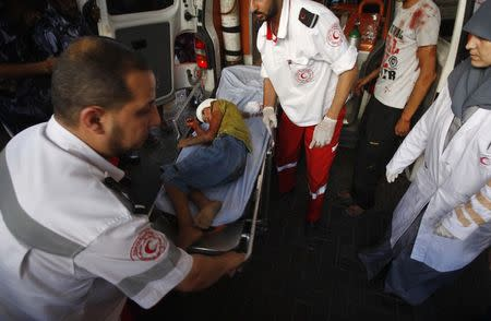 Palestinian medics wheel a stretcher transporting a boy, who hospital officials said was wounded in an Israeli air strike, at a hospital in Gaza City July 11, 2014. REUTERS/Ahmed Zakot