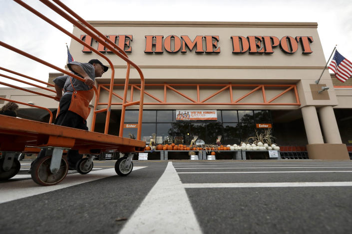 In this Monday, Sept. 23, 2019 photo a worker pushes carts in front of a Home Depot store location, in Boston. (AP Photo/Steven Senne)