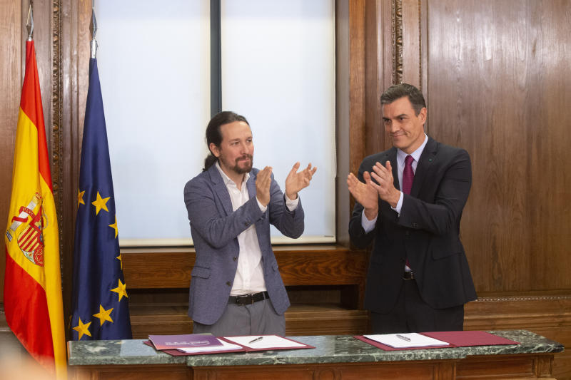 Spain's caretaker Prime Minister Pedro Sanchez, right and Podemos party leader Pablo Iglesias applaud negotiators from both parties after signing an agreement between the two parties in the Spanish parliament in Madrid, Spain, Monday, Dec. 30, 2019. Sanchez hopes to form center-left governing alliance to take office in the country in the coming days. (AP Photo/Paul White)