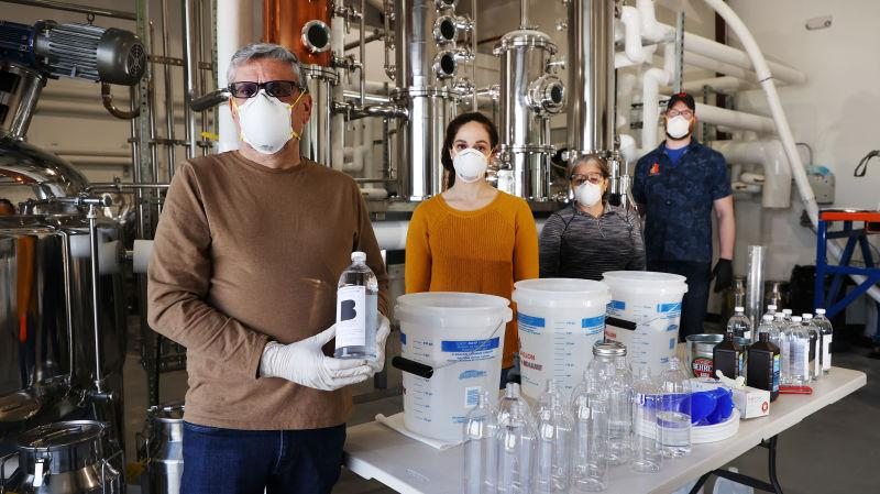 Man holding bottle of hand sanitizer in distillery factory setting