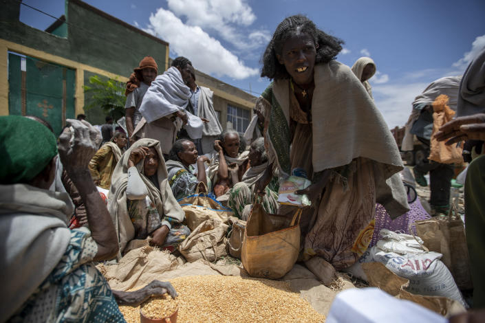 An Ethiopian woman leaves with a portion of yellow split peas after it was distributed by the Relief Society of Tigray in the town of Agula, in the Tigray region of northern Ethiopia, on Saturday, May 8, 2021. The 15 kilograms of wheat, half a kilogram of peas and some cooking oil per person, to last a month — was earmarked only for the most vulnerable. That included pregnant mothers and elderly people. (AP Photo/Ben Curtis)
