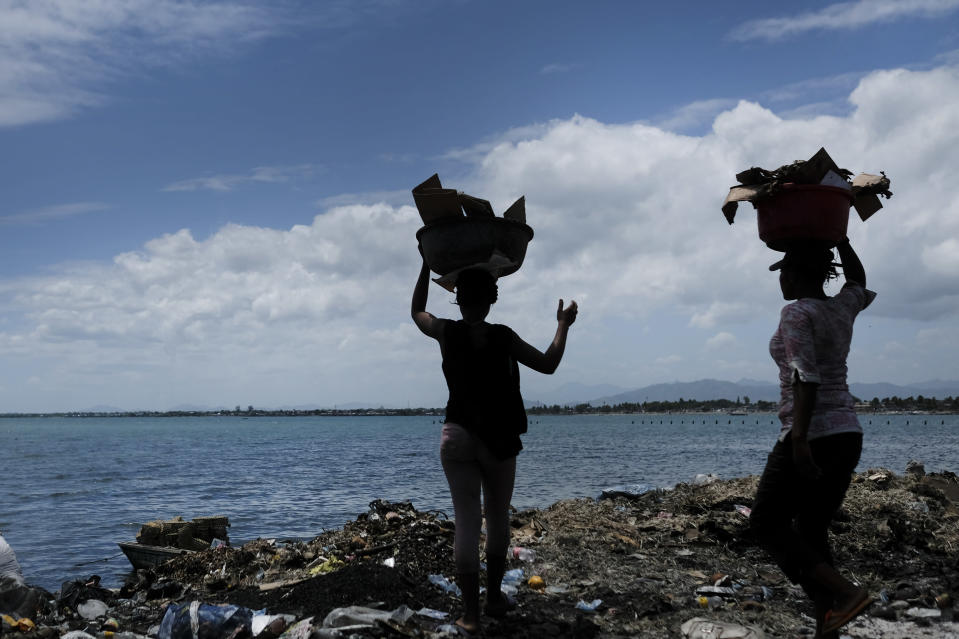 Women carry buckets of trash to the shore on the sidelines of a market in Cap-Haitien, Haiti, Thursday, July 22, 2021. The city of Cap-Haitien is holding events to honor slain President Jovenel Moïse on Thursday ahead of Friday's funeral. (AP Photo/Matias Delacroix)