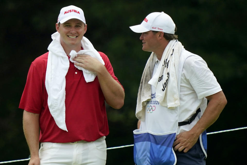 Sepp Straka, of Austria, left, smiles with his caddy on the 15th green during the first round for the men's golf event at the 2020 Summer Olympics, Thursday, July 29, 2021, at the Kasumigaseki Country Club in Kawagoe, Japan, (AP Photo/Matt York)