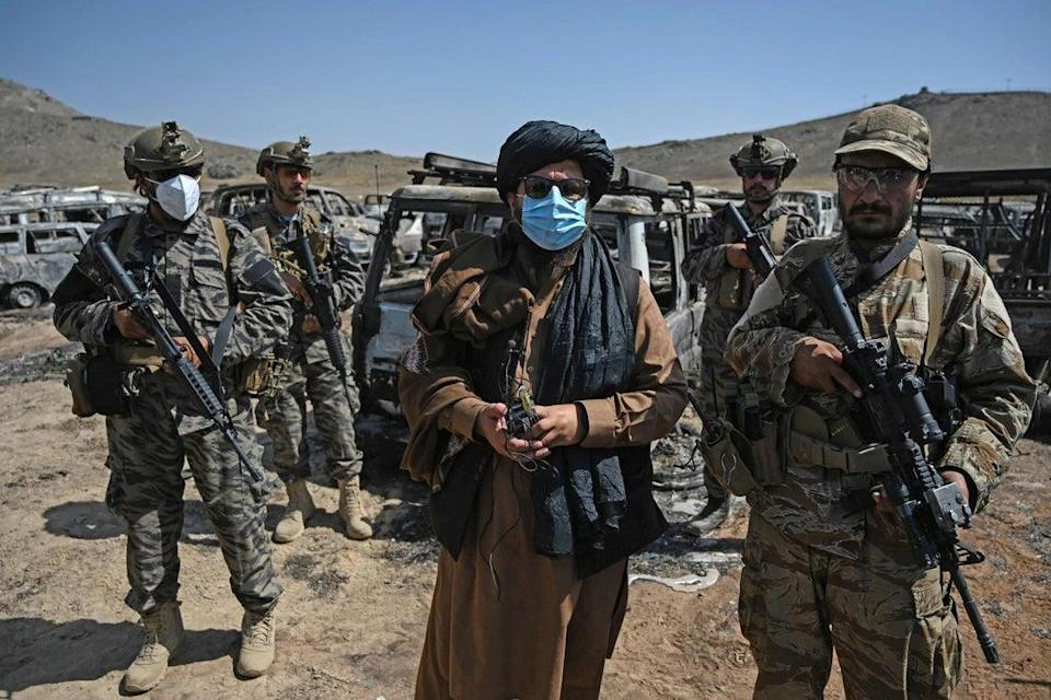 Members of the Taliban Badri 313 military unit stand beside damaged and discarded vehicles parked near the destroyed Central Intelligence Agency (CIA) base in Deh Sabz district northeast of Kabul (AFP via Getty Images)
