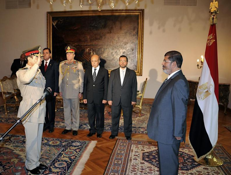 RETRANSMISSION FOR ALTERNATIVE CROP - Egyptian President Mohammed Morsi, right, swears in newly-appointed Minister of Defense, Lt. Gen. Abdel-Fattah el-Sissi, left, in Cairo, Egypt, Sunday, Aug. 12, 2012. Egypt's Islamist president ordered his former defense minister and chief of staff to retire on Sunday and canceled the military-declared constitutional amendments that gave top generals wide powers. (AP Photo/Egyptian Presidency)