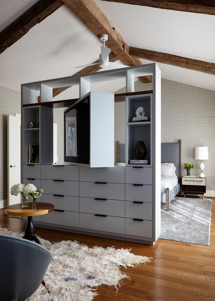 """In the main suite, Liss divided the space with a custom-designed cabinet that includes a rotating TV stand. """"[The room] was 25 feet long, which is almost too much for the space to function properly,"""" says Liss. """"We created a seating area that feels separate."""" The upholstered BDDW bed came from New York, as did the bronze nightstands."""
