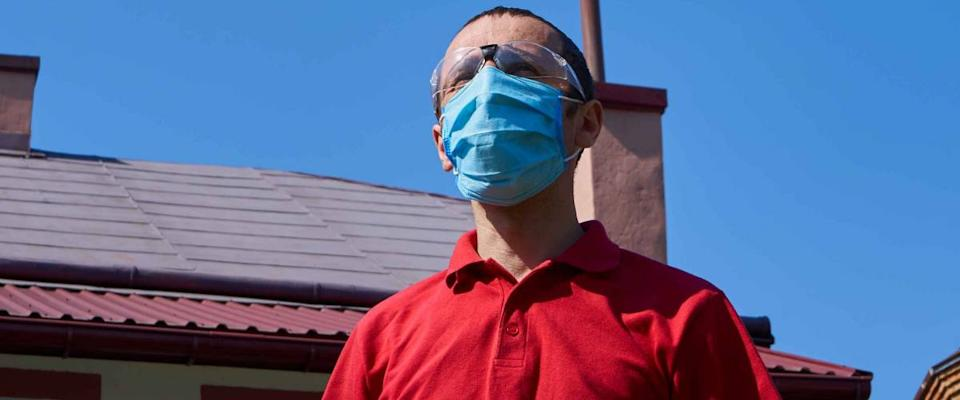 man in a mask on the background of the house,man standing in the yard of his house in a medical mask and glasses
