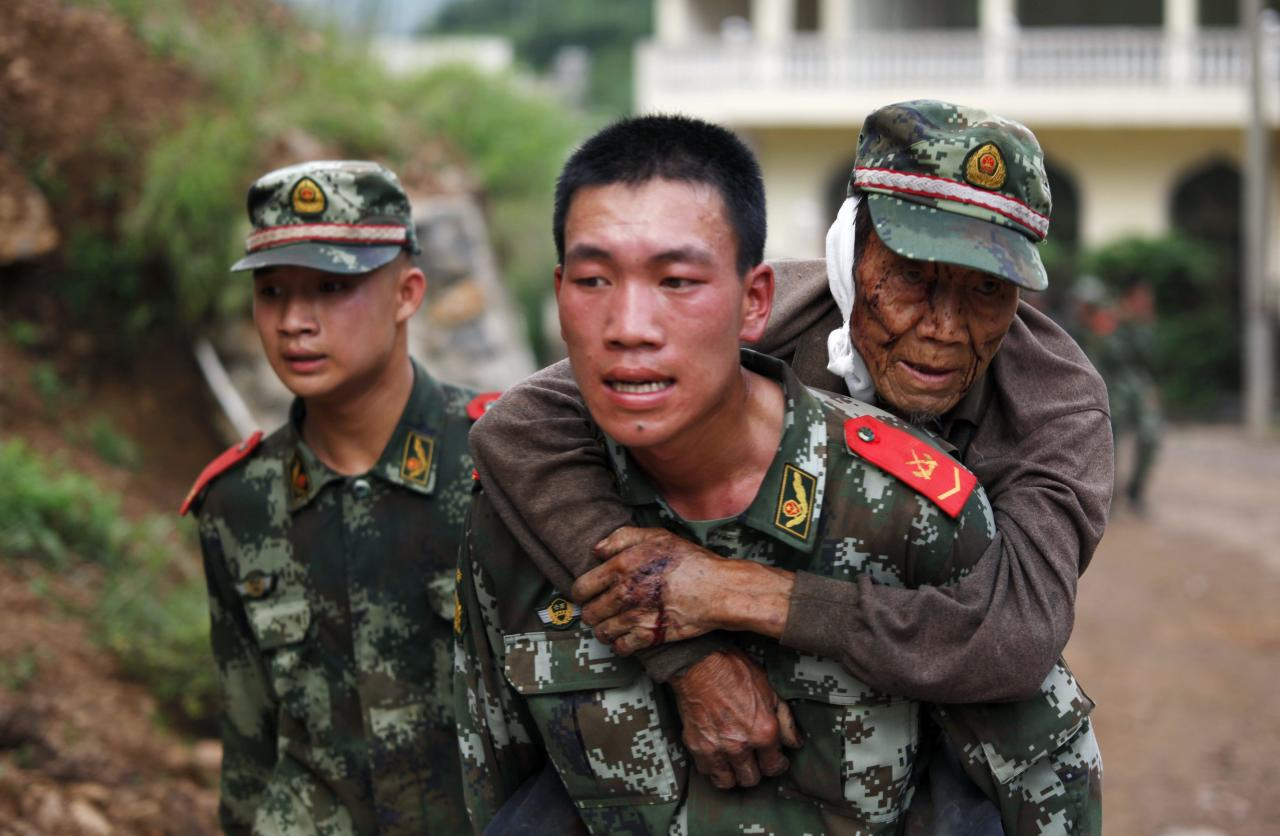 A paramilitary policeman carries an elderly man on his back after an earthquake hit Ludian county of Zhaotong, Yunnan province August 3, 2014. The magnitude 6.5 earthquake struck southwestern China on Sunday, killing at least 150 people in the remote mountainous area of Yunnan province, causing some buildings, including a school, to collapse, Xinhua News Agency reported. REUTERS/China Daily (CHINA - Tags: DISASTER) CHINA OUT. NO COMMERCIAL OR EDITORIAL SALES IN CHINA