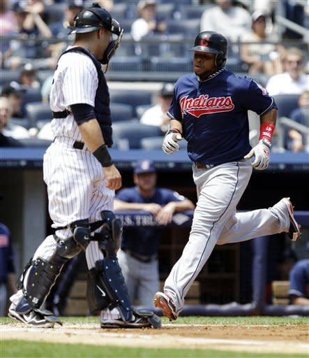 Cleveland Indians' Carlos Santana scores on a hit by teammate Shelley Duncan during the second inning of a baseball game as New York Yankees catcher Russell Martin looks on Wednesday, June 27, 2012, in New York. (AP Photo/Frank Franklin II)