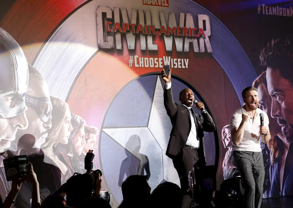 """Actors Chris Evans and Anthony Mackie (L) greet fans during a blue carpet event for the movie """"Captain America: Civil War"""" in Singapore, April 21, 2016. REUTERS/Edgar Su"""