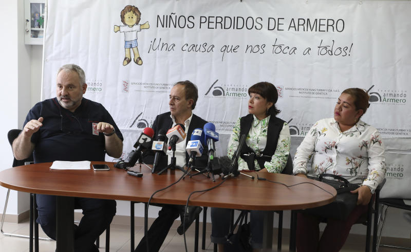 Doctor Juan Yunis, left, talks to the media as Francisco Gonzalez director of the Armando Armero Foundation, second left, Jenifer De La Rosa, second right, and Angela Rendon, left, listen during as press conference in Bogota, Colombia, Thursday, Nov. 14, 2019. The story of the lost sisters could be one of many involving children who were separated from their parents after the Nevado del Ruiz erupted, rescued from the rubble and later put up for adoption after no relative arrived to claim them . A genetic institute in Colombia's capital confirmed through DNA testing that Jenifer De La Rosa and Angela Rendon are sisters. (AP Photo/Fernando Vergara)