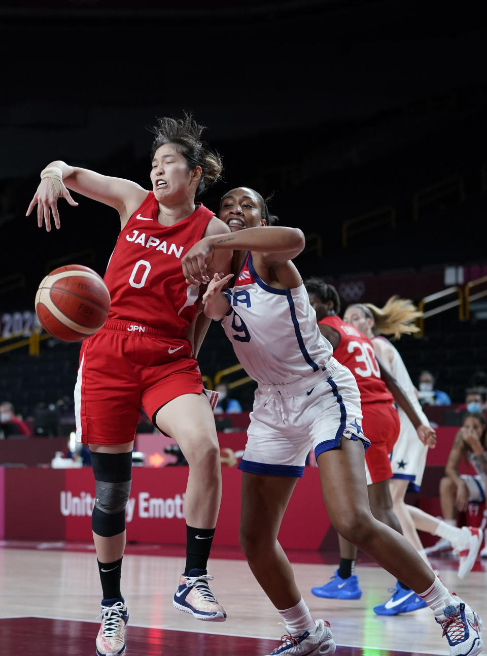Japan's Moeko Nagaoka (0), left, and United States' A'Ja Wilson (9) fight for a rebound during women's basketball preliminary round game at the 2020 Summer Olympics, Friday, July 30, 2021, in Saitama, Japan. (AP Photo/Charlie Neibergall)