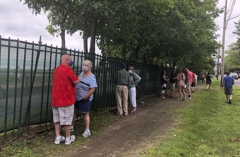 Horse racing fans talk along the fence outside Saratoga Race Course in Saratoga Springs, N.Y., Thursday, July 16, 2020. A Saratoga season like no other is open, with fans barred from attending the start of the 152nd meet in track history and most likely the entire 40 days of racing. (AP Photo/John Kekis)