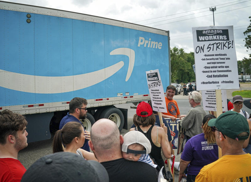 Workers, supporters and activists picket outside the Amazon fulfillment Center in Shakopee, Minn. on the afternoon of Prime Day, Monday, July 15, 2019. Trucks were allowed through the picket line after a brief delay. (Glen Stubbe/Star Tribune via AP)