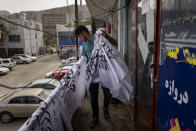 A worker collects newly hand printed Taliban flags in a workshop in Kabul's Jawid market, Afghanistan, Sunday, Sept. 12, 2021. The small flag shop, tucked away in the courtyard of a Kabul market, has documented Afghanistan's turbulent history over the decades with its ever-changing merchandise. Now the shop is filled with white Taliban flags, emblazoned with the Quran's Muslim statement of faith, in black Arabic lettering. (AP Photo/Bernat Armangue)