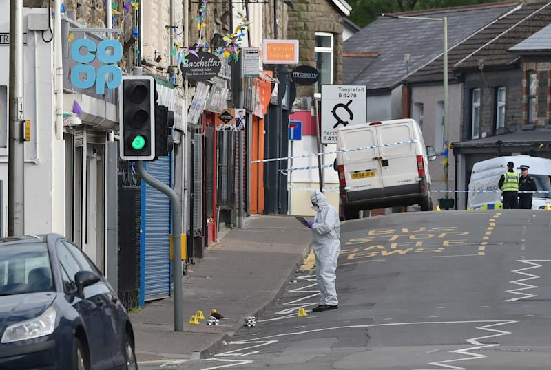 Forensic officers at the scene of a reported stabbing in the village of Pen Y Graig in South Wales.