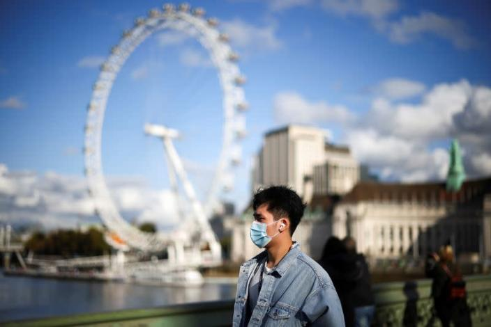A man wearing a protective face mask walks across Westminster bridge, during the coronavirus disease (COVID-19) outbreak, in London