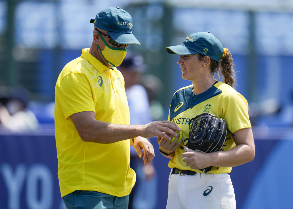 Australia's pitcher Kaia Parnaby is substituted by a coach during the softball game between Japan and Australia at the 2020 Summer Olympics, Wednesday, July 21, 2021, in Fukushima , Japan. (AP Photo/Jae C. Hong)