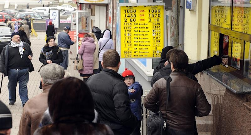 People queue at an exchange counter in central Kiev on February 28, 2014