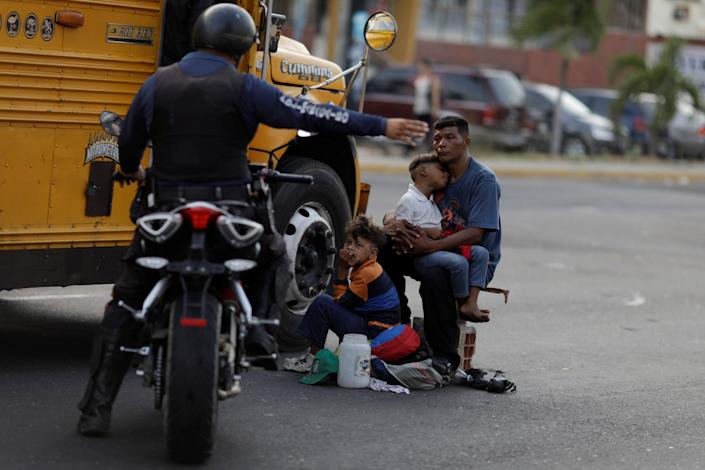 A Venezuelan police officer orders a man and his sons to move from the street where he was asking for donations during a blackout in Maracaibo, Venezuela. (Photo: Ueslei Marcelino/Reuters)
