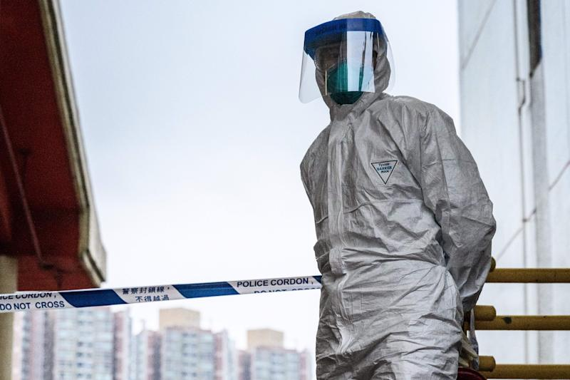 A police officer wearing protective gear stands in front of a cordon outside Hong Mei House at the Cheung Hong Estate in Hong Kong on February 11, 2020, following the evacuation of more than 100 people from the housing block after four residents in two different apartments tested positive for the new coronavirus. - Officials said the relocation of residents in Tsing Yi district was a precautionary measure after three members of the same family contracted the virus. (Photo by Anthony WALLACE / AFP) (Photo by ANTHONY WALLACE/AFP via Getty Images)