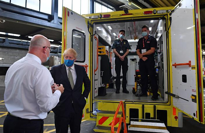 Boris Johnson talks with London Ambulance Service CEO Garrett Emmerson after meeting brothers Jack Binder, a paramedic, and Tom Binder, a firefighter, on Monday. (Ben Stansall/pool/AFP via Getty Images)