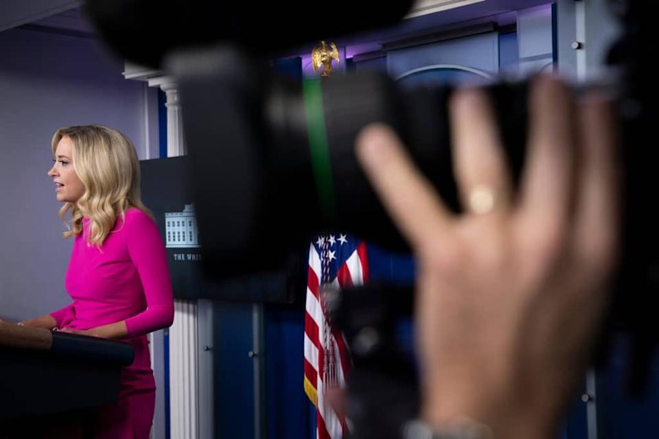 Kayleigh McEnany speaks in a pink dress behind the White House Briefing Room press podium