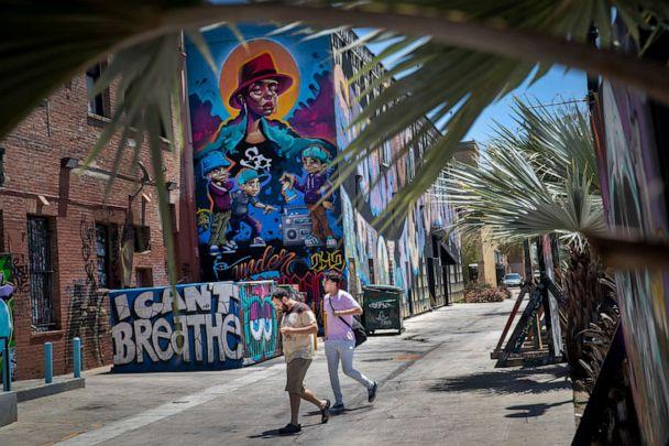 PHOTO: Pedestrians not wearing masks walk past murals in downtown Santa Ana, Calif., July 7, 2020. (Los Angeles Times via Getty Images)