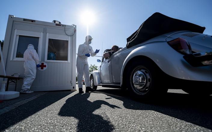 Mandatory Credit: Photo by LUKAS BARTH-TUTTAS/EPA-EFE/Shutterstock (10727582c) A volunteer from the Bavarian Red Cross is testing a traveler at a coronavirus test station at the service area Hochfelln-Nord on the A8 motorway between Salzburg and Munich near Bergen, Bavaria, Germany, 30 July 2020. Travelers entering Bavaria now have the opportunity to be tested for the COVID-19 coronavirus voluntarily and free of charge at airports, motorways and railway stations. Testing for coronavirus at motorway near German-Austrian border, Bergen, Germany - 30 Jul 2020 - LUKAS BARTH-TUTTAS/EPA-EFE/Shutterstock