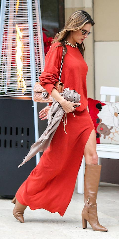 <p>Alessandra Ambrosio wore a red dress with leather Jimmy Choo boots, a chunky gold necklace, and a Chanel bag.</p>