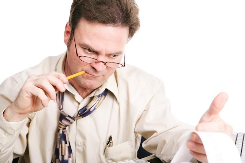 An accountant chewing on a pencil while critically analyzing figures from his printing calculator.