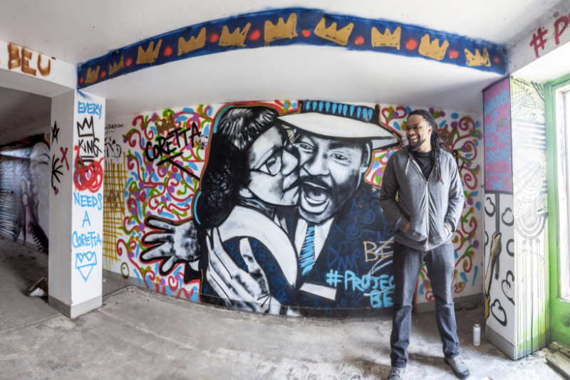 """Brandan Odums in front of a portrait of Coretta Scott King and Martin Luther King Jr. in his """"Project Be"""" space in 2013. (Brandan Odums)"""