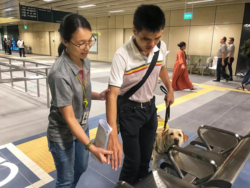 An SMRT Buses staff member aiding a visually-impaired commuter with a guide dog at the upcoming Yishun Integrated Transport Hub on 23 August, 2019. (PHOTO: SMRT)