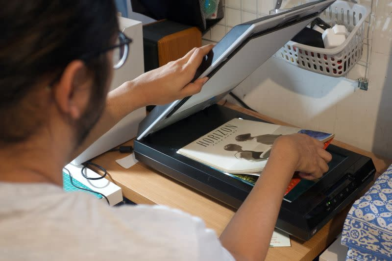 Ais, a 29-year-old LGBT+ researcher, puts a copy of Indonesia's decades-old LGBT+ magazine on a scanner while digitising it in Jakarta, Indonesia