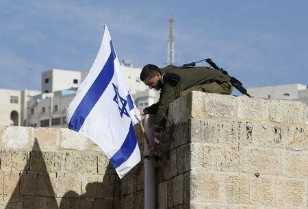 Israeli soldier removes the Israeli flag from a house as Israeli troops forcibly remove Jewish settlers from homes, in the West Bank city of Hebron