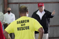President Donald Trump speaks with first responders as he tours a warehouse being used as a distribution point for relief aid after Hurricane Laura hit the area, Saturday, Aug. 29, 2020, in Lake Charles, La. (AP Photo/Alex Brandon)
