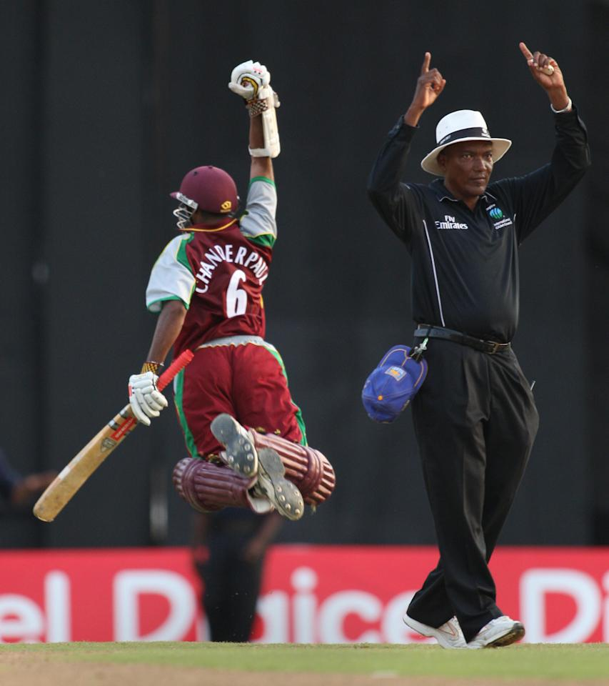 As umpire Clay Duncan (R) signals, West Indies batsman Shivnarine Chanderpaul (L) jumps to celebrate his six that won the match on the last ball against Sri Lankan bowler Chaminda Vaas (not pictured) on April 10, 2008 at the Queens Park Oval in Port of Spain, Trinidad and Tobago, during the first of three One-Day International matches between West Indies and Sri Lanka.  West Indies won 236 for 9 to Sri Lanka's 235 for 7.   AFP PHOTO/Stan HONDA (Photo credit should read STAN HONDA/AFP/Getty Images)