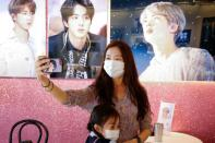 Kang Lucia, fan of K-pop boy band BTS, takes a selfie at a cafe decorated with photos and merchandise of them, in Seoul