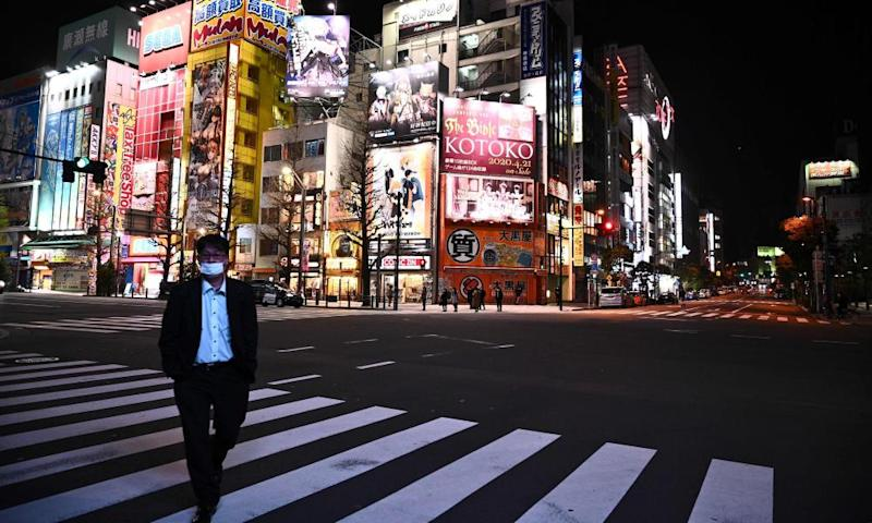 A man wearing a face mask walks across the road in the Akihabara district of Tokyo.