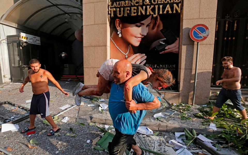 A man carried an injured girl through debris in the Achrafiyeh district of Lebanon - GETTY IMAGES