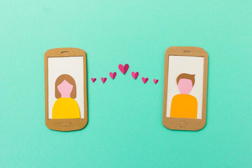 Online dating and mobile flirting concept - man and woman profile on smartphones connected with flying paper hearts
