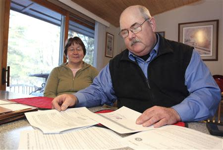 Retired Wisconsin State Trooper Keith Young and his wife Michelle look at paper work at their home in Elk Mound, Wisconsin March 22, 2014. REUTERS/Andy Clayton-King