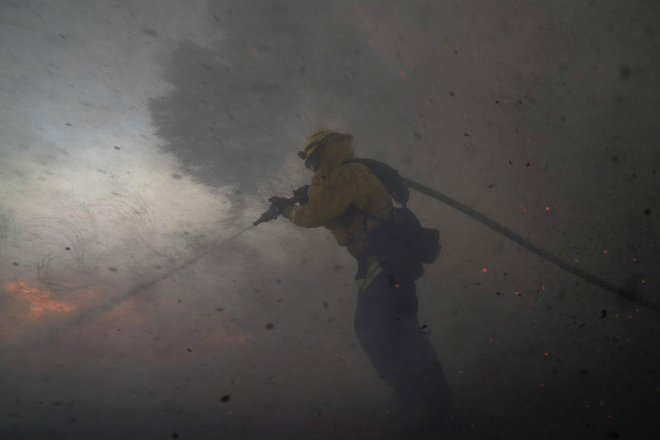 A firefighter battles the Silverado Fire Monday, Oct. 26, 2020, in Irvine, Calif. A fast-moving wildfire forced evacuation orders for 60,000 people in Southern California on Monday as powerful winds across the state prompted power to be cut to hundreds of thousands to prevent utility equipment from sparking new blazes. (AP Photo/Jae C. Hong)