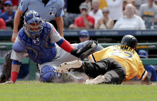 Pittsburgh Pirates pinch runner Kevin Newman, right, is tagged out by Chicago Cubs catcher Willson Contreras as he tries to score from second on a double by Starling Martein the seventh inning of a baseball game, Sunday, Aug. 19, 2018, in Pittsburgh. The Pirates challenged the call, but it was held up on review. (AP Photo/Keith Srakocic)