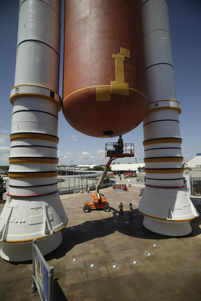 In this June 20, 2013 photo, workers put the finishing touches on the entrance to the space shuttle Atlantis attraction at the Kennedy Space Center Visitor Complex in Cape Canaveral, Fla. The 900,000 square-foot facility centering around Atlantis will open to the public June 29. (AP Photo/John Raoux)