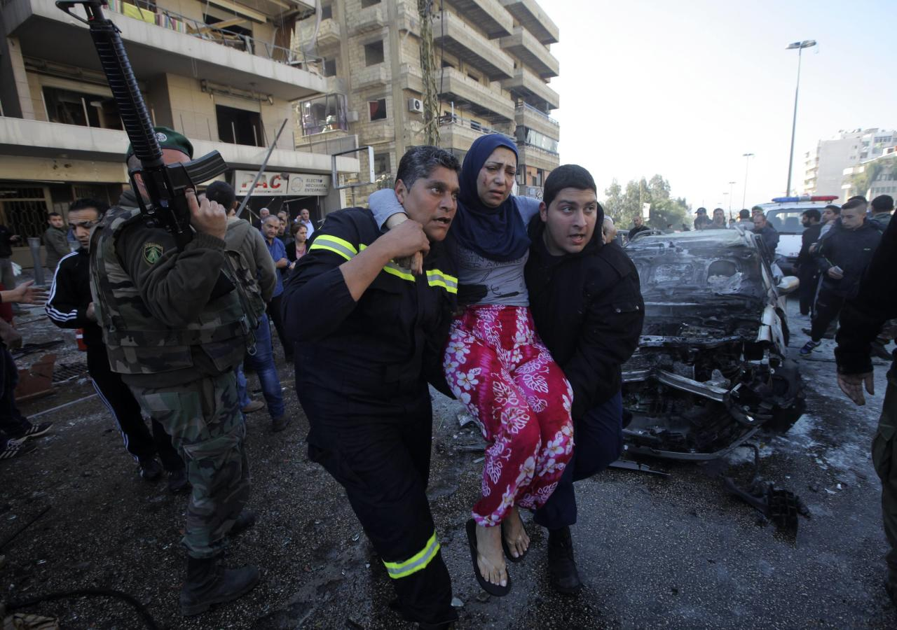 Civil defence members carry a wounded woman as a Lebanese Army soldier secures the area at the site of an explosion in the southern suburbs of Beirut February 19, 2014. The explosion on Wednesday appeared to be caused by a twin bomb attack using a car and a motorcycle, security sources said. REUTERS/Mahmoud Kheir (LEBANON - Tags: POLITICS CIVIL UNREST TPX IMAGES OF THE DAY)