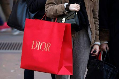 A shopper carries a Dior shopping bag as she takes care of her last-minute Christmas holiday gift purchases in Paris, France, December 18, 2017. REUTERS/Charles Platiau