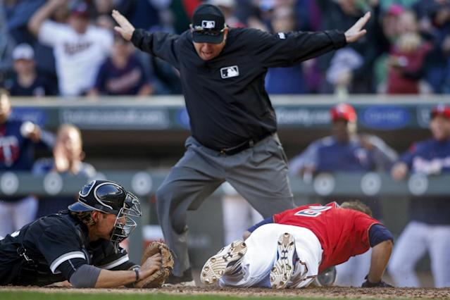 Brian Dozier looks at the ump after sliding into home to complete an inside-the-park home run (AP Photo/Bruce Kluckhohn).