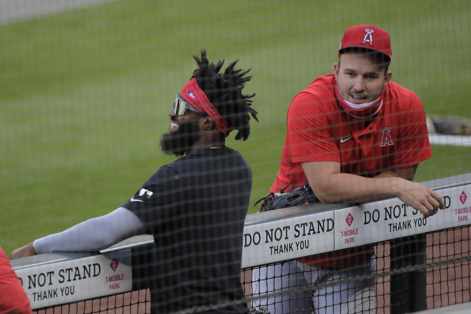 Los Angeles Angels center fielder Mike Trout, right, talks with Brian Goodwin, left, before a baseball game against the Seattle Mariners, Tuesday, Aug. 4, 2020, in Seattle. (AP Photo/Ted S. Warren)